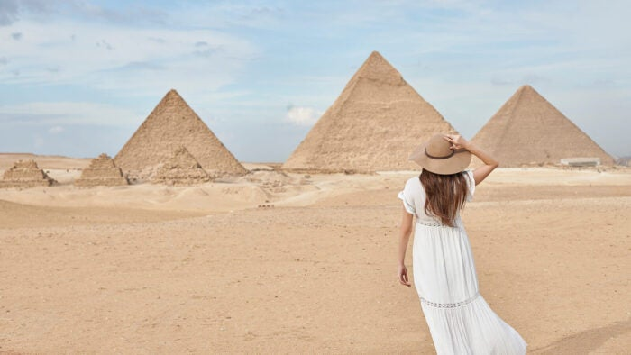 woman in front of pyramids in egypt