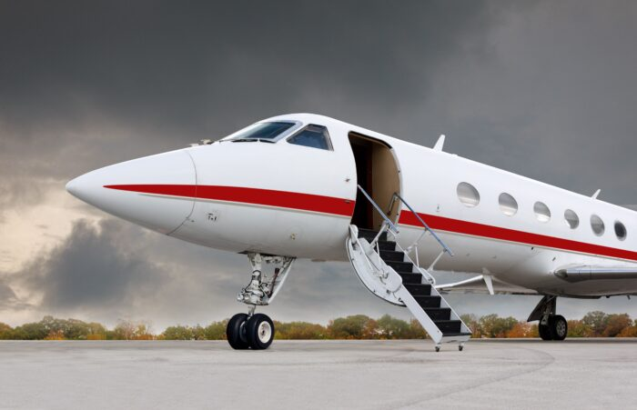 red and white business jet on runway