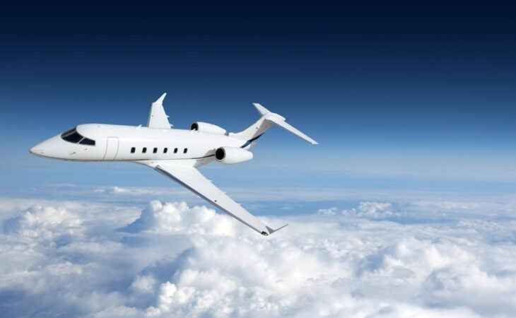 white private jet flying in clouds