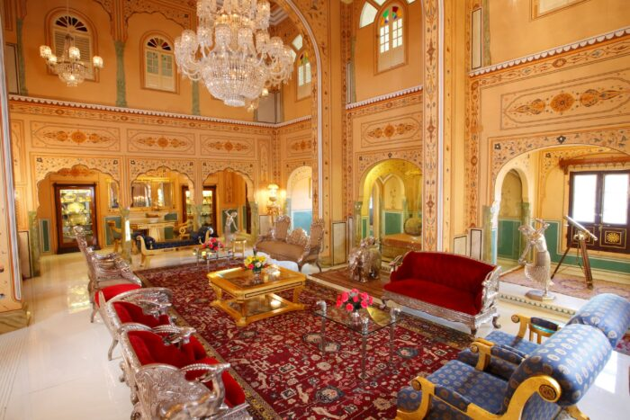 The pavilion suite lounger at the Raj Palace with rich red furniture and a huge chandelier