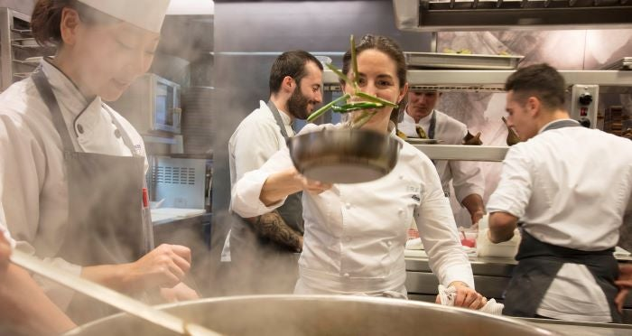 Elena from Arzak cooking in busy kitchen