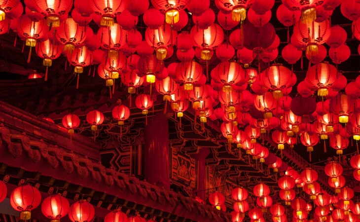 100's of red lanterns hang on strings around a temple