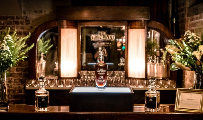 Bottle of Glenlivet Scotch stands on bar between two whisky decanters