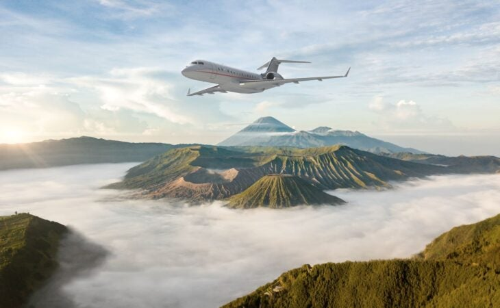 VistaJet plane flying over mount