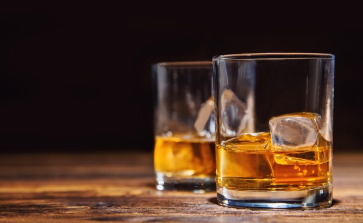 two glasses of bourbon on wooden table