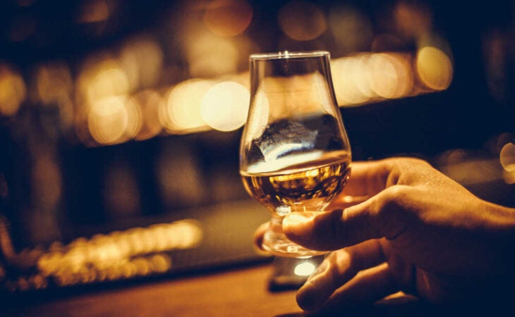 Hand holding a whiskey tasting glass- Difference between Irish Whiskey and Scotch