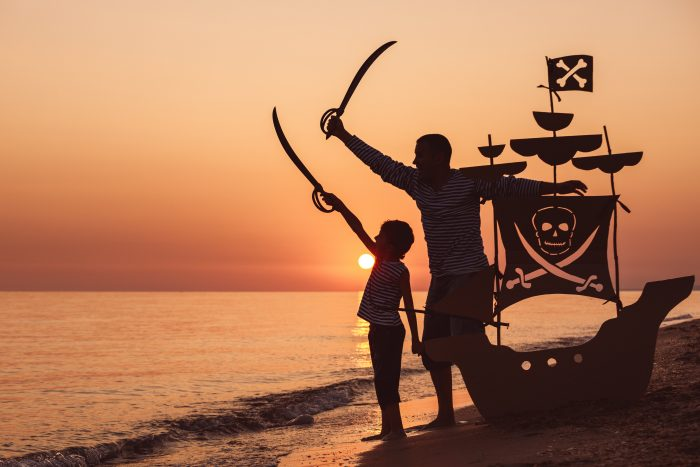 Father and Son pretend to be pirates on beach at sunset - Family Vacation