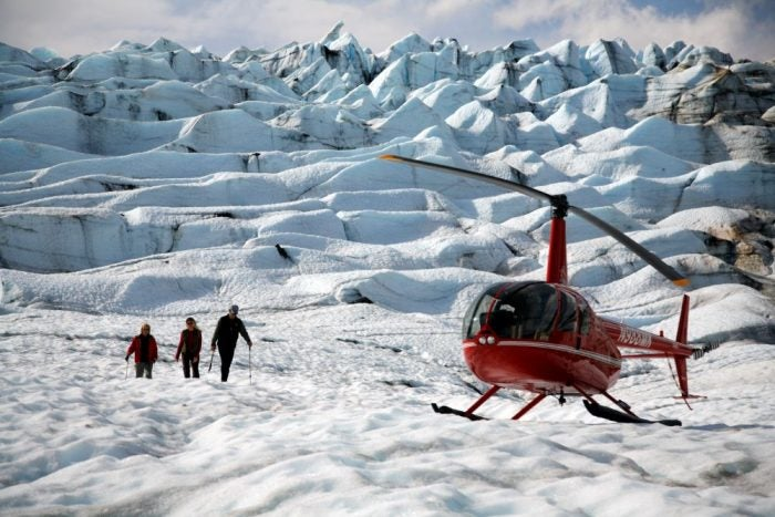 Helicopter landing to pick up hikers at snowy glacier - Family Vacation