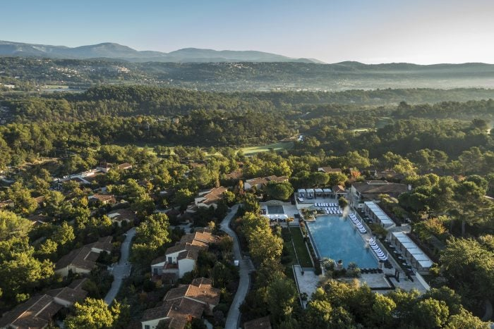 Aerial shot of resort with trees and pool