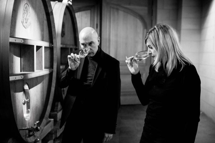 Two of Telmont's team members sample wine straight from the barrel.