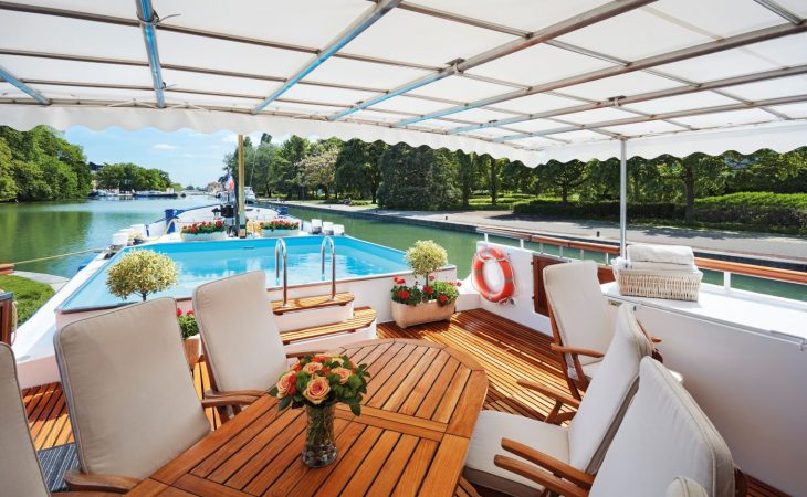 Deck of Belmond Barge featuring dining table and pool