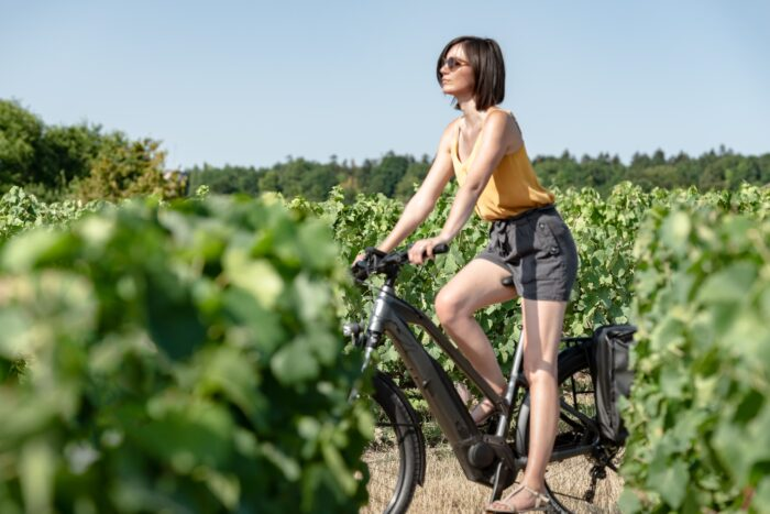 woman cycling through vineyards in champagne